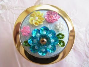 直径4㎝の蓋つきのケースです。蓋の部分にビーズ刺繍をした生地を貼ります。ブルー、ピンク、黄色の花が刺してあります。