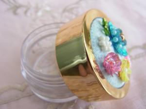 蓋にパステル調の4種の花が刺繍されている、小さいアクリルケースです。