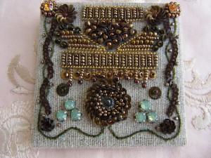 ワイヤーで長方形や三角形を作り中をビーズと金属製のモールで刺し埋めます。下部にボリュームのある花を刺繍し、両サイドにもレーヨン糸と小さいスパンコールで刺繍をします。正方形の土台に刺繍をした生地を被せ、金具を縫いとめた裏生地を貼りあわせます。
