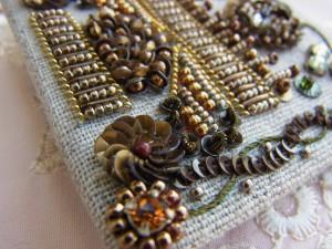 両サイド上部に2つの花があります。レーヨン糸を蛇行させながら刺繍した上に、小さいスパンコールを蛇行方向が重ならないように刺繍していきます。