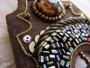 ブローチの下部は、スパンコールの上に金属製のモールを縄状に刺繍し、その下に色とりどりのビーズを隙間なく刺繍ています。