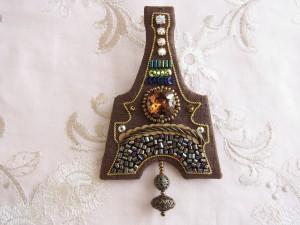 インドシルクの生地にワイヤーでエッフェルト塔の形を作り、中央にスモークトパーズを配置しその上下にビーズやスパンコールなどで刺繍をします。エッフェル塔の形の土台に刺繍をした生地を被せ、メタルビーズを挟み金具を縫いとめた裏生地を貼りあわせます。