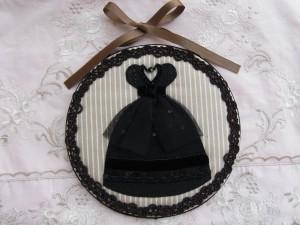 ドレスの形にカットしたフェルトを生地に接着し、チュールやビーズ、スパンコールなどで刺繍した後、丸い土台に被せリボンを挟んで裏生地を貼りあわせます。