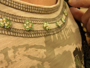 Tシャツの首元に、スパンコールとビーズを使ったお花が横一列に刺してあります。