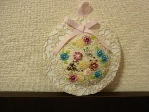 円形の壁飾りです。スパンコールで刺した様々なお花があります。上部にはリボンを飾っています。