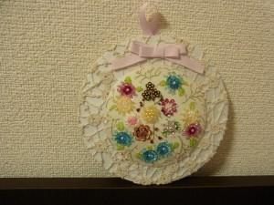 円形の壁飾りです。スパンコールで刺した様々なお花があります。上部には可愛いリボンが飾ってあります。