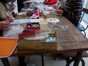 大きなテーブルを囲んでビーズ刺繍をしています。