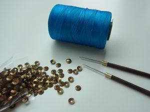 レーヨン糸と針とスパンコールです。