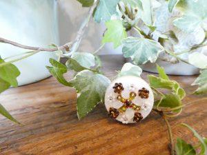 円形のブローチです。スパンコールを使った立体的なお花や、ビーズで作った可愛い小花が刺繍してあります。中央の花びらは、スイカの種の様なビーズを使っています。