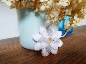 大小の花びらを重ねたブローチです。花芯部分にガラス玉2個を飾りました。