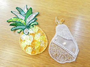 アリワークでビーズ刺繍したパイナップルと洋梨です。輪郭に沿ってカットしています。