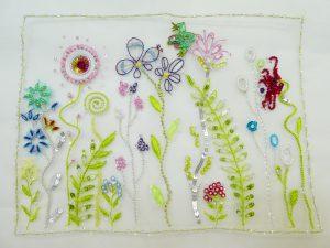 アリワークでビーズ刺繍をしています。スパンコールと糸刺繍を組み合わせたお花がたくさん刺してあります。お花の間からカエルが顔を出しています。