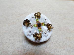 直径3cmのブローチです。中心のビジューの周りに、ビーズとスパンコールで刺したお花がバランスよく配置してあります。