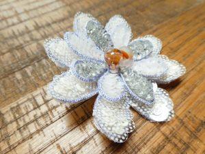 大小の花びらを重ねたブローチです。花芯は大きなカラス玉を飾っています。