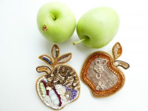 アリワークで刺した繊細なリンゴのブローチと、観賞用のリンゴです。