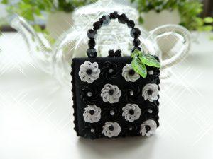 正方形のバック型のブローチです。モノトーンの立体的な小花が16個並んでいます。
