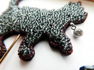 極小ビーズ刺し埋めたネコのブローチです。首元には鈴の代わりにクリスタルを飾っています。