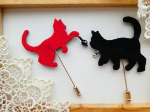 2匹のネコのブローチの裏面は赤と黒になっています。首元にクリスタルを飾っているネコと前足にボールを持っているネコがいます。