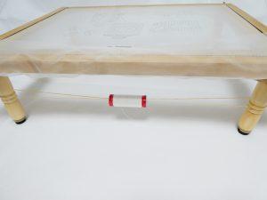 刺繍枠の2本足に輪ゴムを掛けています。輪ゴムの中央に糸がセットしてあります。