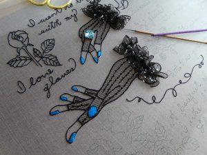 手袋をはめた両手が刺繍されています。