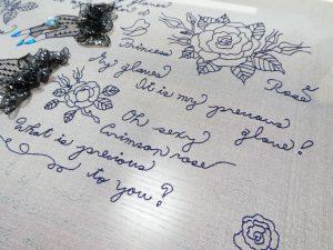 細い糸で刺した英字と薔薇の花です。