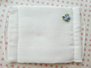 白いガーゼのマスクに小花の飾りを縫い留めました。
