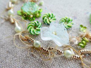 半透明の花形ビーズの周りにパールと綱状に刺したモールがあります。
