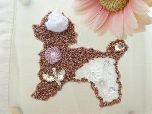 アリワークで刺した犬です。レースとリボンを使ったお花模様ができています。