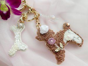 モコモコの犬と骨とクリスタルの飾りが付いたバックチャームです。