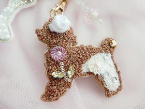 モコモコの犬です。尻尾にビジューがあり、顔の下にスパンコールで刺した円形のお花あります。