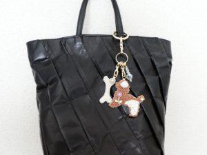 モコモコの犬と骨とクリスタルの飾りが付いたバックチャームです。黒のバックにつけています。
