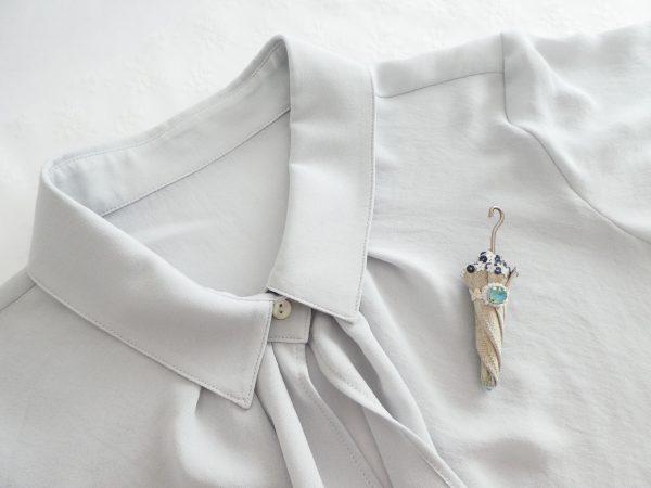 落ち着いた色合いの傘ブローチを洋服に付けています。中央の大きなビジューがキラキラ輝いています。