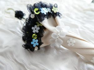 傘の形のブローチです。ヒラヒラのオーガンジーリボンに、爽やかな色の小花のスパンコールが沢山刺してあります。ドロップビーズを巻いて束ねています。持ち手にも花の形のオーガンジーリボンを飾っています。