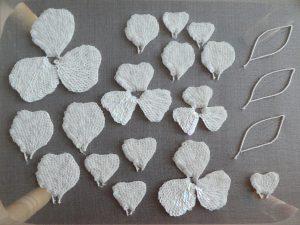 スパンコールで刺繍した3枚連なった花びらと、1枚づつの花びらがあります。