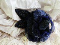 紺色の薔薇のブローチです。スパンコールで刺繍した花びらの間に、オーガンジーのリボンが入っています。