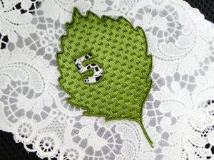 光沢のある糸で刺繍をした葉っぱのブローチです。羽根とクリスタルが刺繍してあります。数字の5が切り抜きしてあります。