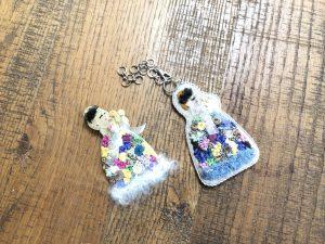 ドレスを着た女性のバックチャームです。ビーズとスパンコールの花とリボン刺繍の模様が華やかです。