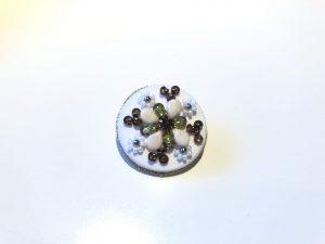 円形のブローチです。中央のビジューの周りに、ビーズとスパンコールを組み合わせて十字に刺繍しています。外側にビーズで作った円形にのお花があります。