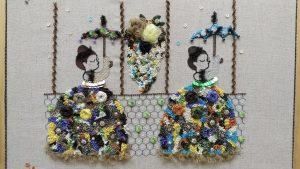アリワークとリボン刺繍のコラボ作品です。傘を刺している女性が2人並んでいます。スパンコールとリボンで刺繍した華やかなドレスをきています。