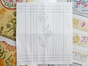 アリワーク体験のサンプルデザインです。縦横ラインと中央にお花がデザインされています。