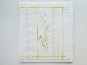中央にビーズで刺したお花があります。その周りを縦と横のラインで囲っています。アリワークの体験用のサンプルです。