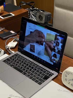 パソコンにビーズ刺繍をしている手元が写っています。