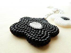 黒と白の花がペアーになったバックチャームです。両面にビーズが刺繍されている黒いお花です。