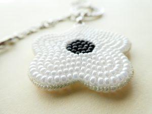 黒と白の花がペアーになったバックチャームです。両面にビーズが刺繍されている白いお花です。