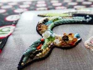 クジラの尻尾です。先端に立体的なお花があります。その周りをビーズやモールで囲うように刺繍しています。