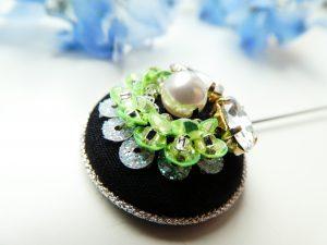 ハットピンブローチです。中央のパールを半円状にビーズとスパンコールを一緒に刺繍した列で囲んでいます。もう一方の半円にはダイヤ型ビジューが2つ葉っぱの様に刺繍してあります。