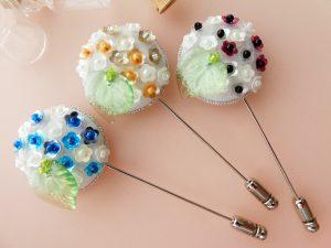 ハットピンブローチです。3本並んでいます。どれも小さい花形ビーズが円形にたくさん刺繍してあります。左下には透き通った葉っぱ型のビーズが刺繍してあります。