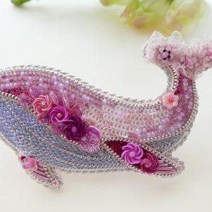 全体がピンク色で統一されているくじらのブローチです。胴体にはスパンコールで刺繍した小花があります。尻尾はフサフサのリボンと花形スパンコールが刺繍してあります。お腹は光沢のある糸で刺繍してあります。