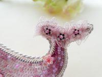 全体がピンク色で統一されているくじらのブローチです。尻尾はフサフサのリボンと花形スパンコールが刺繍してあります。