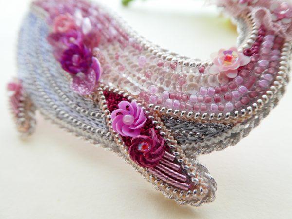 全体がピンク色で統一されているくじらのブローチです。お腹は光沢のある糸でサテンステッチしてあります。ヒレにも小花が刺繍してあります。